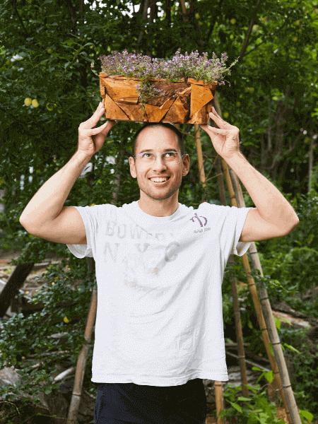 Mann mit Kräuterkiste am Kopf
