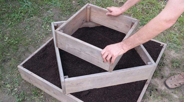 Auf den zweiten Holzrahmen folgt diagonal der dritte. Dadurch entstehen wieder Ecken – wobei diesmal nur jeweils eine Saatkartoffel in jede Ecke gelegt wird.