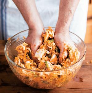 Mann arbeitet Kimchi-Paste in Schüssel voll Kraut ein