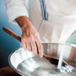 Koch streut Salz ins Wasser