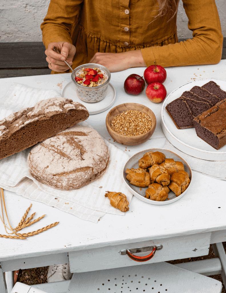 Brot, Gebäck, Müsli, Äpfel auf weißem Tisch