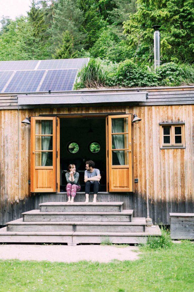 zwei Personen sitzen vor Tiny House